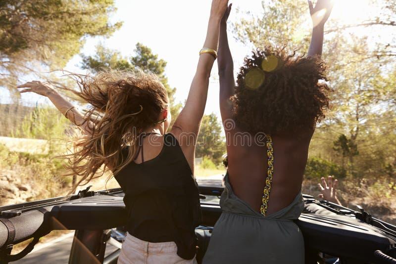 Zwei aufgeregte Frauen stehen auf der Rückseite des Großraumwagens, hintere Ansicht stockfoto
