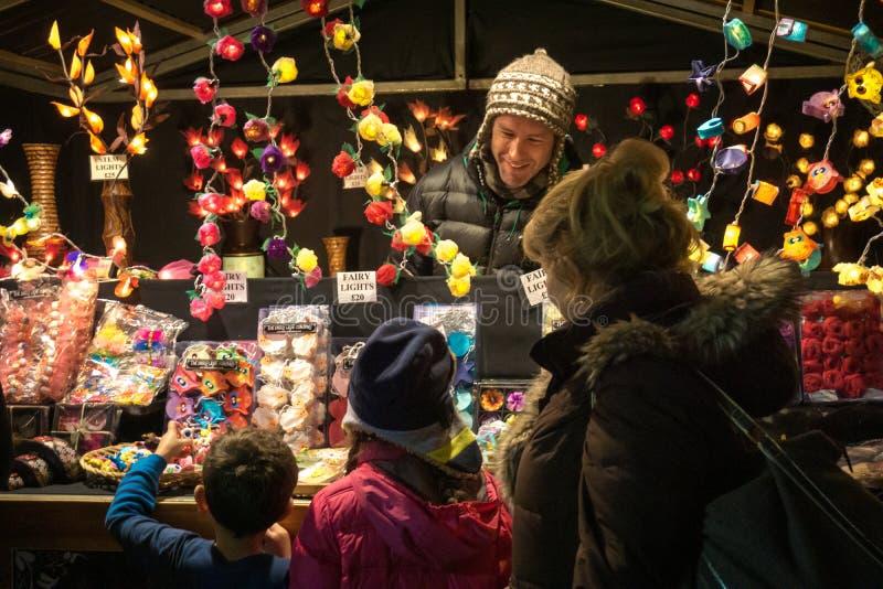 Zwei aufgeregte Kinder mit ihrer Gro?mutter in einem Weihnachtsmarkt lizenzfreie stockfotos