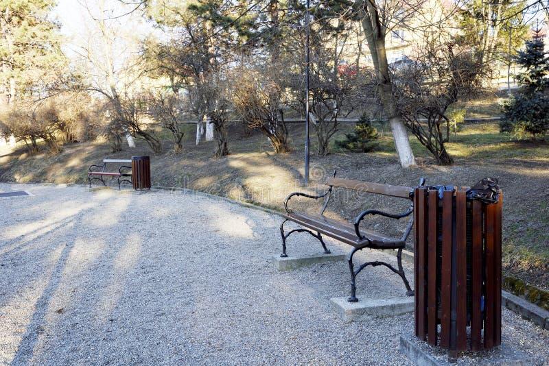 Zwei Bänke in einem Park und in hölzernen Mülleimern lizenzfreies stockfoto