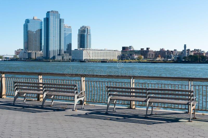Zwei Bänke entlang des East River in Richtung Brooklyn in New York City lizenzfreies stockbild