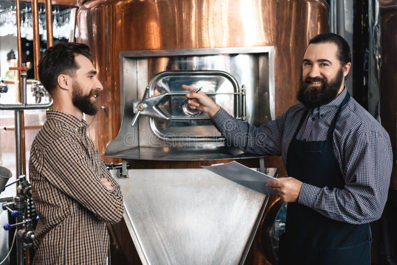 Zwei bärtige Brauer prüfen Ausrüstung der Brauerei auf Produktion des Handwerksbieres über brauen brauerei lizenzfreies stockbild