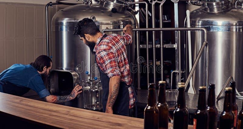 Zwei bärtige Hippie-Männer in einem Schutzblech, das in einer Brauereifabrik arbeitet stockbild