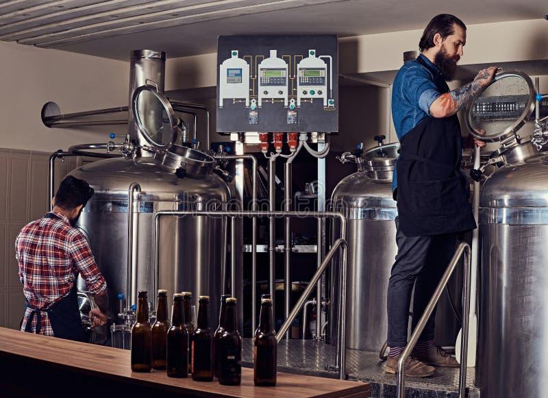 Zwei bärtige Hippie-Männer in einem Schutzblech, das in einer Brauereifabrik arbeitet lizenzfreie stockbilder