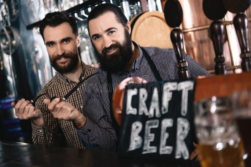 Zwei bärtige Männer halten in den Pfeifen des Handtabaks und stehen nahes Zeichen mit Aufschrift Handwerks-Bier lizenzfreies stockfoto