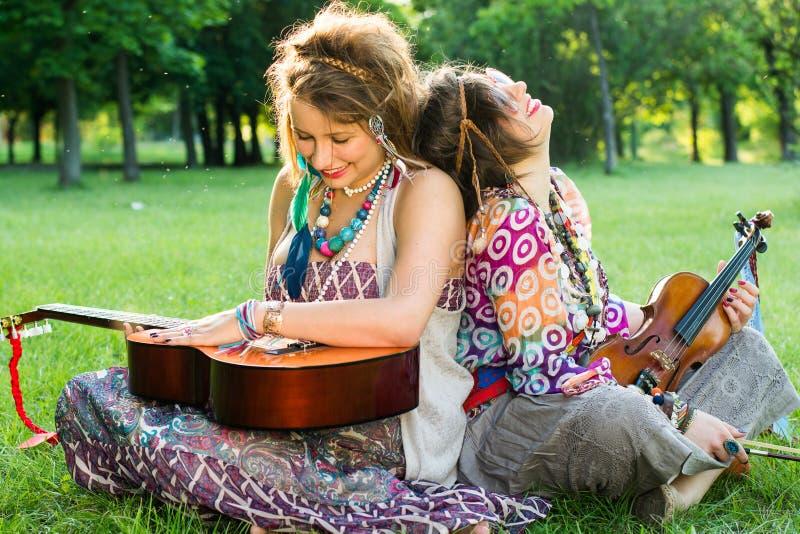 Zwei böhmische Musiker, die auf dem Gras sitzen lizenzfreie stockbilder