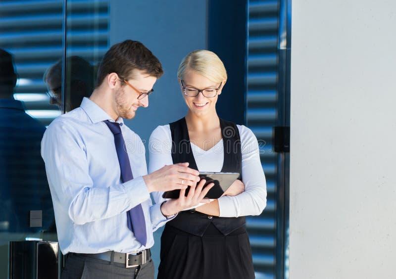 Zwei Büroangestellte, die Spaß mit einer Tablette haben lizenzfreie stockfotografie