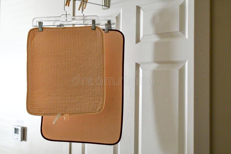 Zwei Badwolldecken, die an der Badezimmertür gehangen werden, um von einer vor kurzem genommenen Dusche auszutrocknen lizenzfreie stockfotos