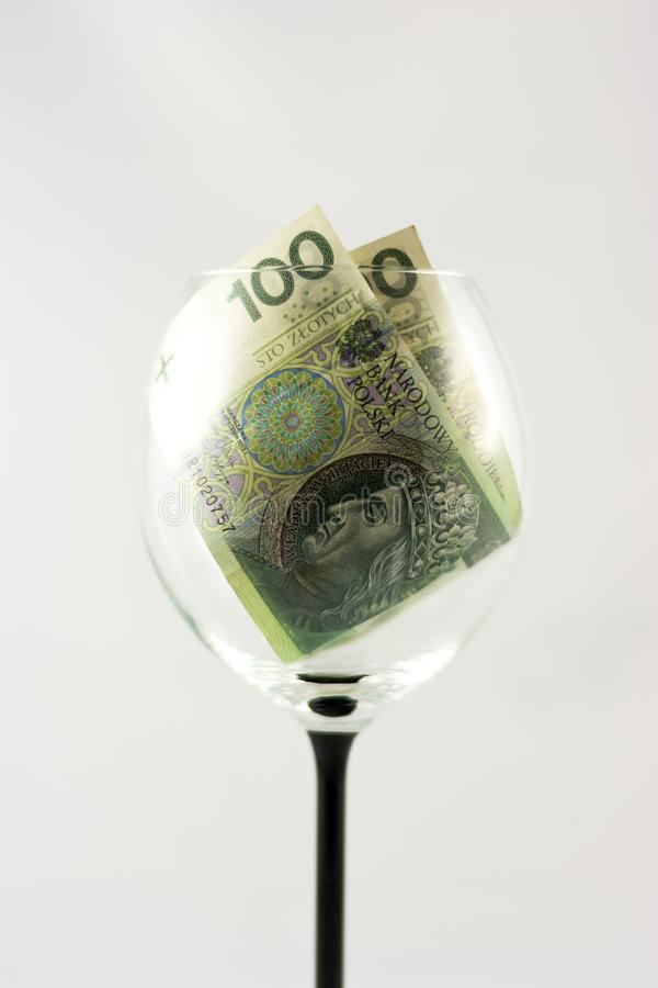 Zwei Banknoten hundert polnische Zlotys innerhalb des Weinglases lizenzfreie stockfotografie