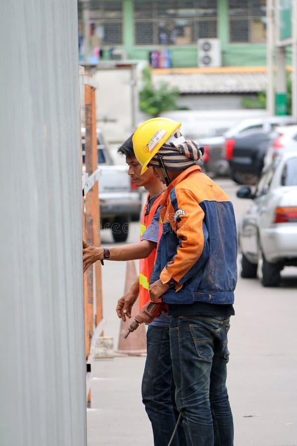 Zwei Bauarbeiter in der orange und blauen Kleidung, welche die Zinkwand durch elektrische Bohrmaschine bohrt lizenzfreie stockbilder