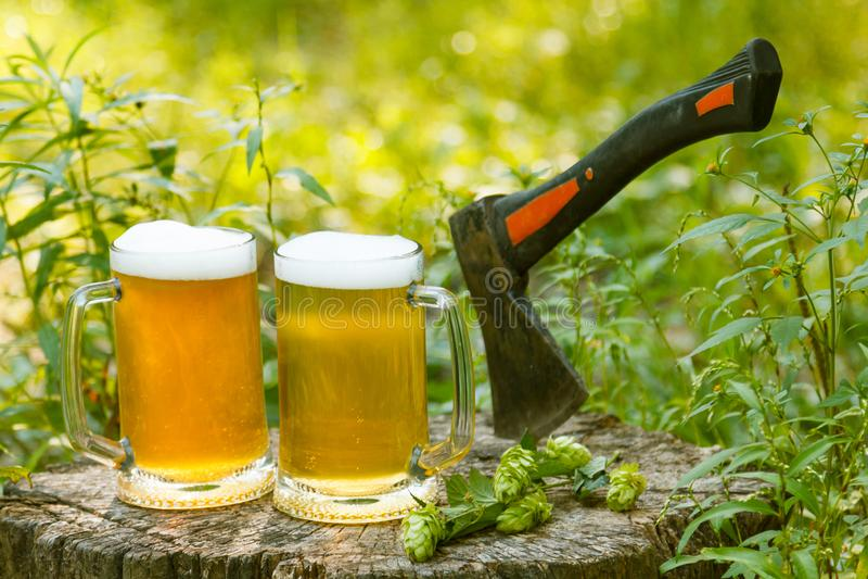 Zwei Becher helles Bier mit Axt gegen Hintergrund von den grünen Bäumen im Freien lizenzfreie stockfotografie