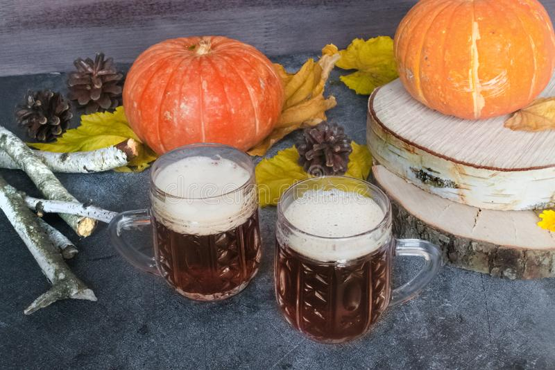 Zwei Becher kaltes dunkles Bier mit Kürbisen und Herbstlaub auf einem hölzernen Hintergrund Halloween-Jahreszeit Biertag stockfotografie
