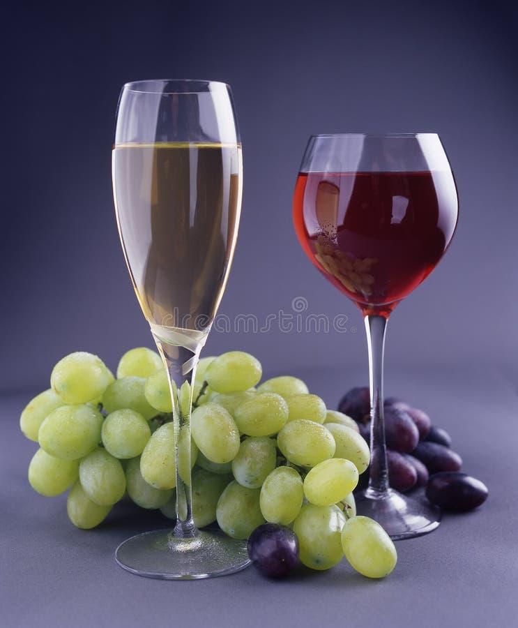 Zwei Becher mit Wein und Traube stockbilder