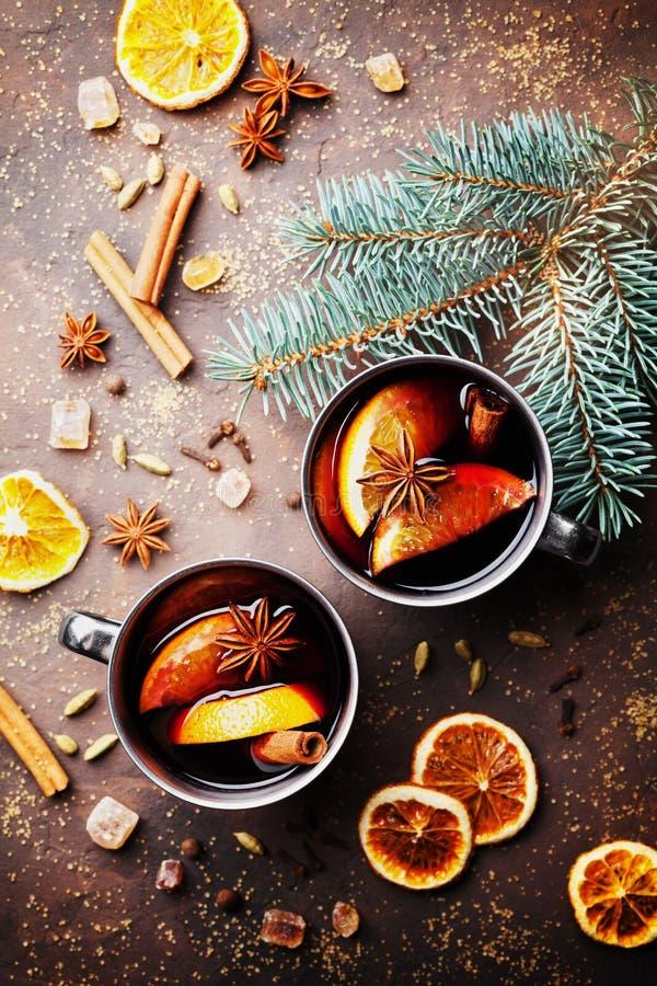 Zwei Becher Weihnachtenglühwein oder gluhwein mit Gewürzen und orange Scheiben auf rustikaler Tischplatteansicht Traditionelles G stockfoto