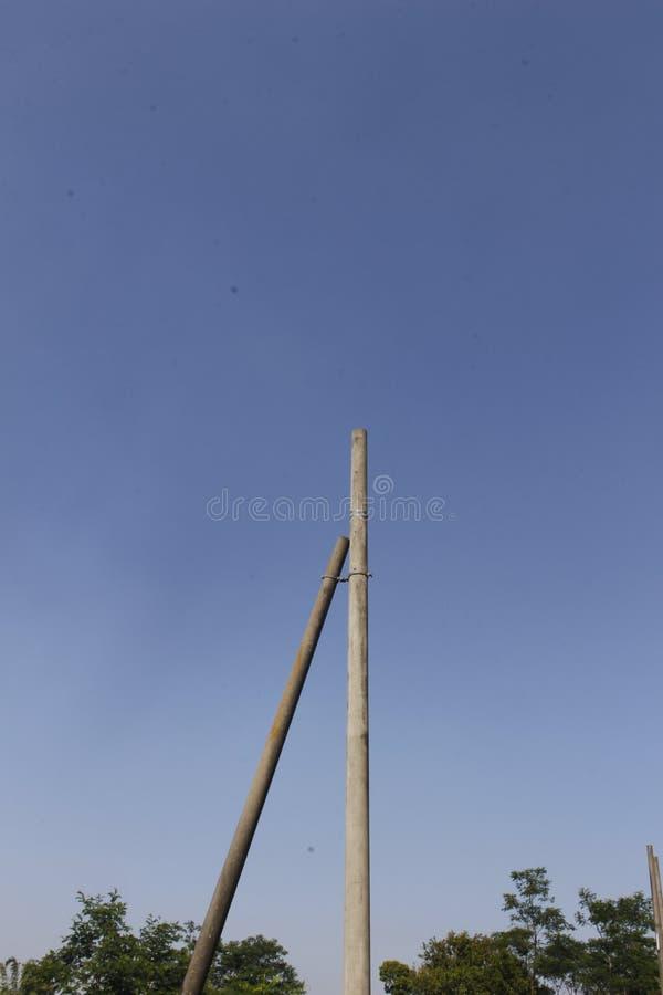 Zwei behinderte elektrische Pole 1 mit einem Minimalismus für den blauen Himmel stockbild