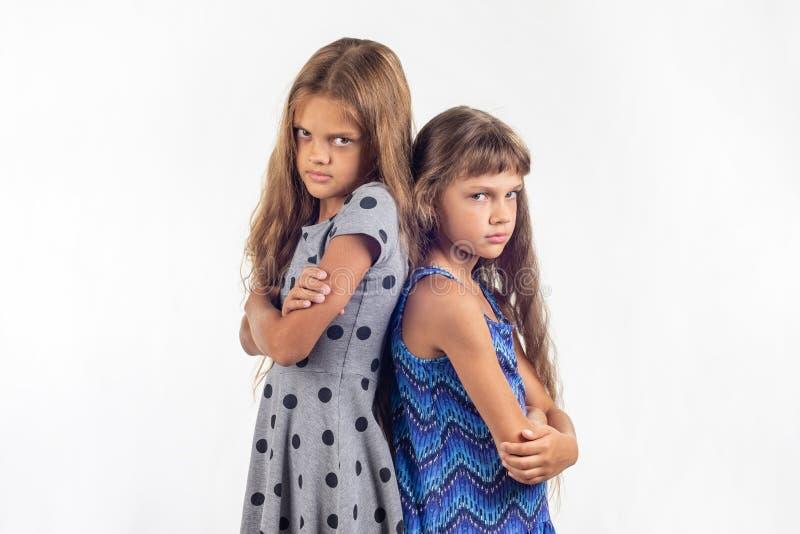 Zwei beleidigte Mädchen stehen mit ihren Rückseiten miteinander stockbilder