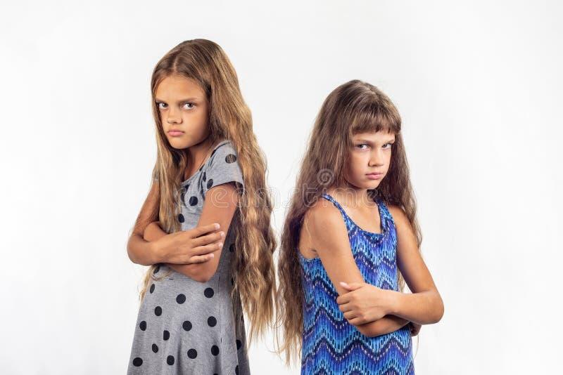 Zwei beleidigte Mädchen stehen mit ihren Rückseiten miteinander stockbild