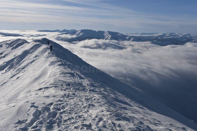 Zwei Bergsteiger auf einem Berg übersteigen im Winter lizenzfreies stockbild