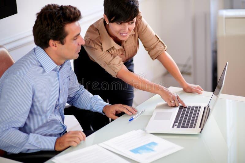 Zwei Berufskollegen, die Computer betrachten stockbild