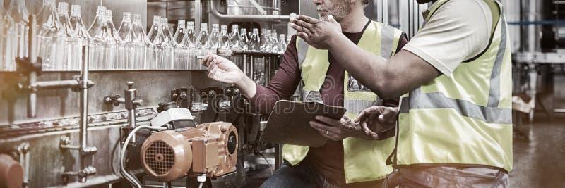 Zwei besprechende Arbeiter, bei der Überwachung Fertigungsstraße trinkt lizenzfreie stockfotografie