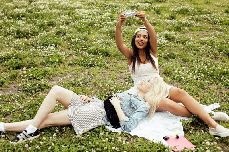 Zwei beste Freunde der jungen hübschen Jugendlichmädchen, die auf das Gras macht selfie Foto hat Spaß, Lebensstilglückliche mensc lizenzfreie stockfotografie