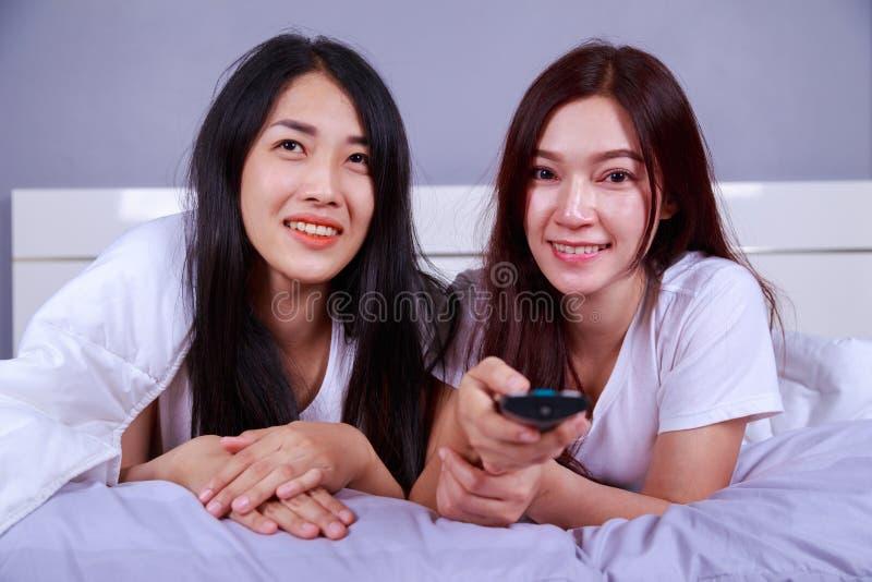Zwei beste Freunde, die mit Direktübertragung auf Bett im Schlafzimmer fernsehen stockbilder
