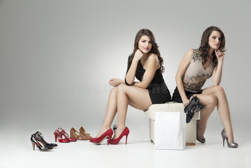 Zwei bezaubernde Frauen, die hohe Absätze versuchen lizenzfreies stockfoto