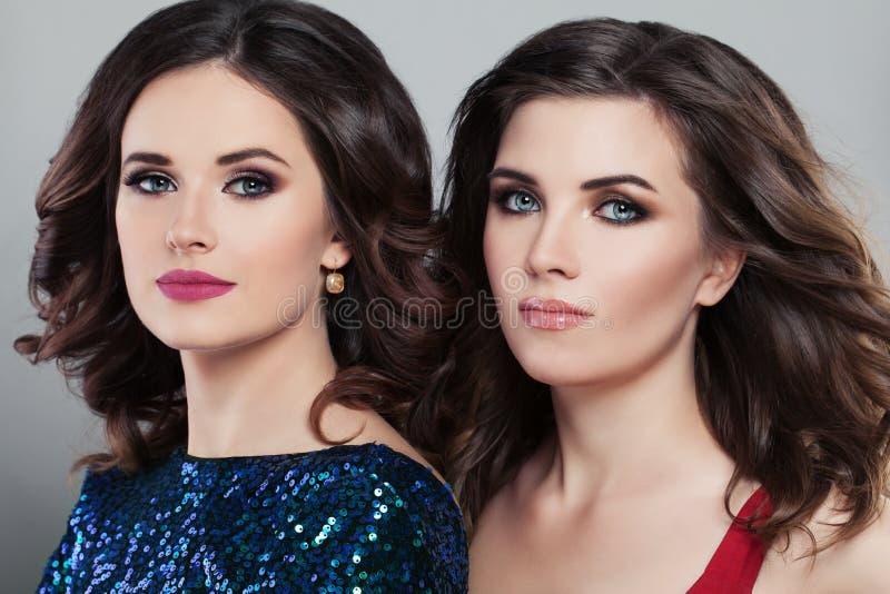 Zwei bezaubernde Frauen-Mode-Modelle Abendfrisur und -make-up lizenzfreies stockbild