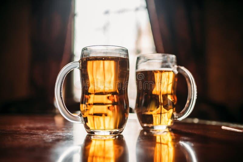 Zwei Bierkr?ge auf h?lzernem Barz?hler, Makroansicht lizenzfreie stockfotos