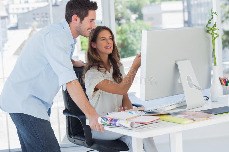 Zwei Bildeditoren, die an einem Computer arbeiten lizenzfreie stockfotografie