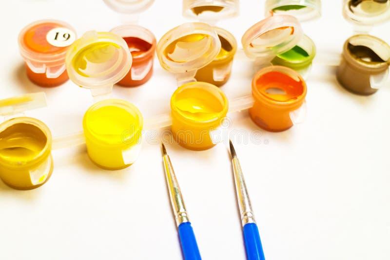 Zwei blaue Pinsel für Farbe auf einem weißen Hintergrund nahe bei ihnen Behälter mit Farbengouache stockfoto