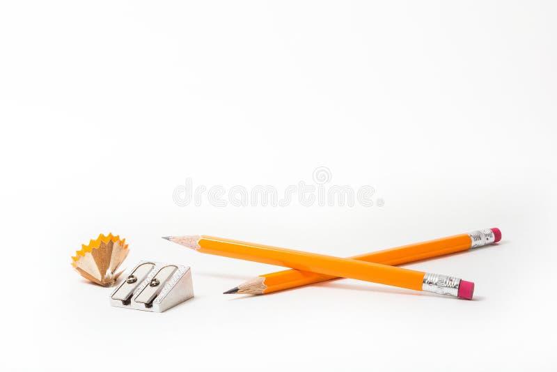 Zwei Bleistifte mit Bleistiftspitzer und schärfen Schnitzel auf weißem Hintergrund briefpapier stockfotografie