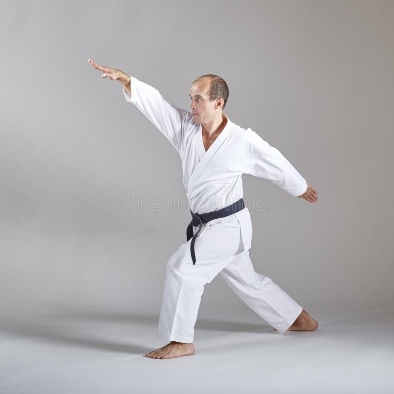 Zwei Blockhände, die der Sportler im karategi auf einem grauen Hintergrund ausbildet lizenzfreies stockbild