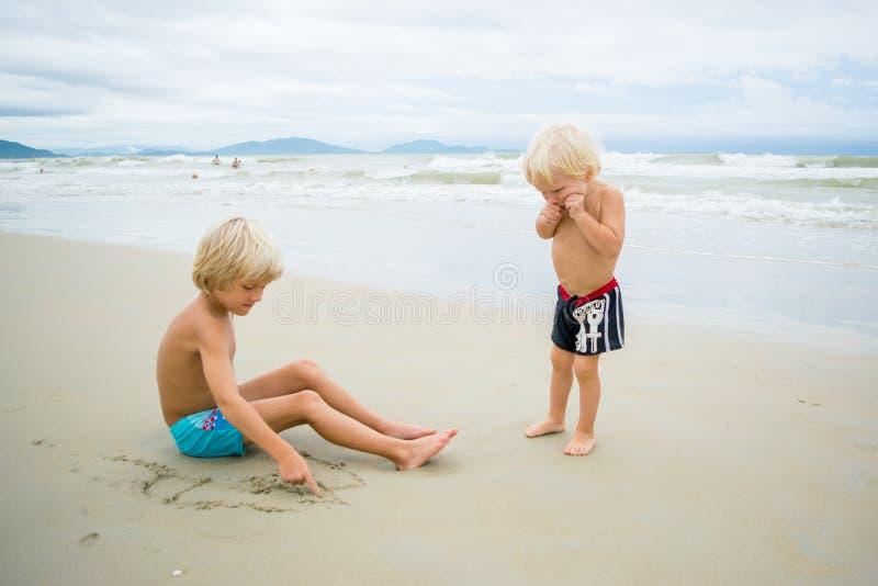 Zwei blonde Brüder, die im Sand nahe dem Meerwasser an einem Strand spielen lizenzfreies stockbild