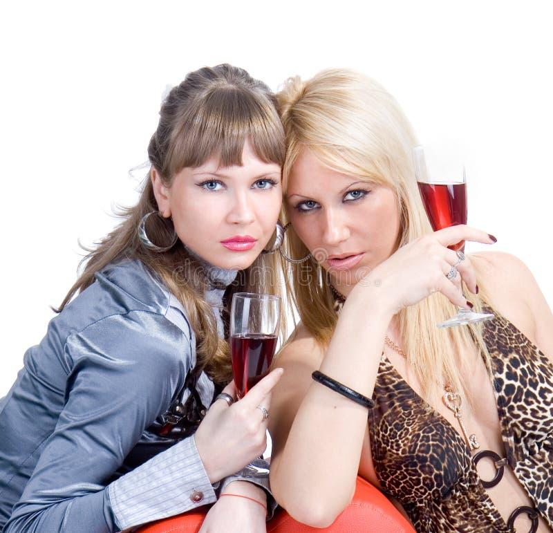 Zwei blonde Mädchen sind bestätigen Rotwein lizenzfreie stockbilder
