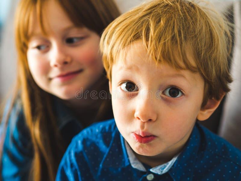 Zwei blonde nette Kinder in den blauen Hemden stockfotos