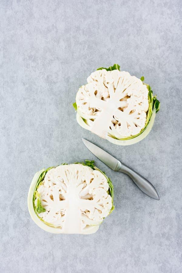 Zwei Blumenkohl-Hälften und Messer auf Gray Background stockfotos