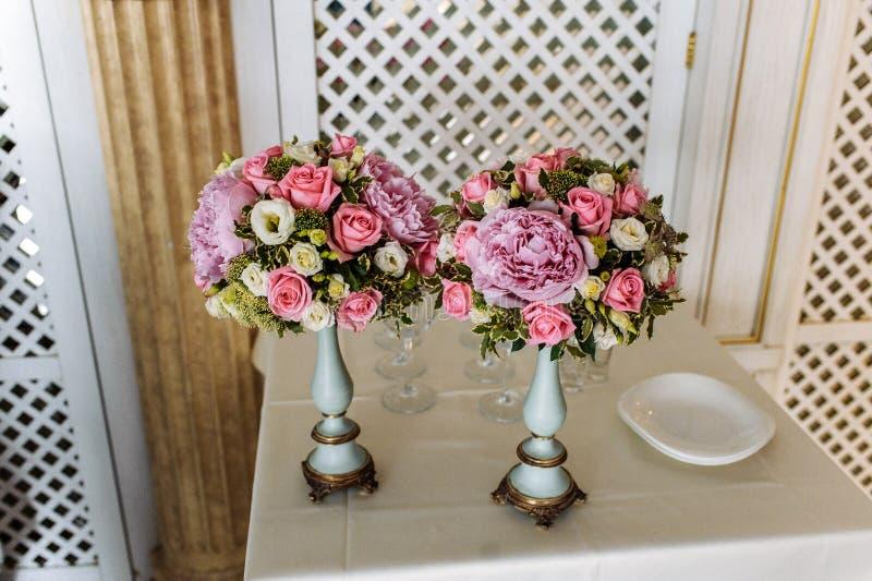 Zwei Blumensträuße von Rosen und von Pfingstrosen in den eleganten Vasen auf einem hellen Hintergrund lizenzfreie stockfotos