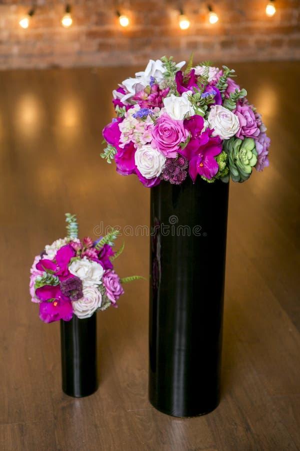 Zwei Blumensträuße von schönen Mischblumen in den schwarzen Vasen Reizender Blumenstrauß Arbeit des Berufsfloristen Wedding oder  lizenzfreies stockfoto