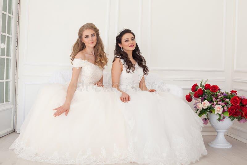 Zwei Bräute in den Brautkleidern sitzen auf einer weißen Couch stockfoto