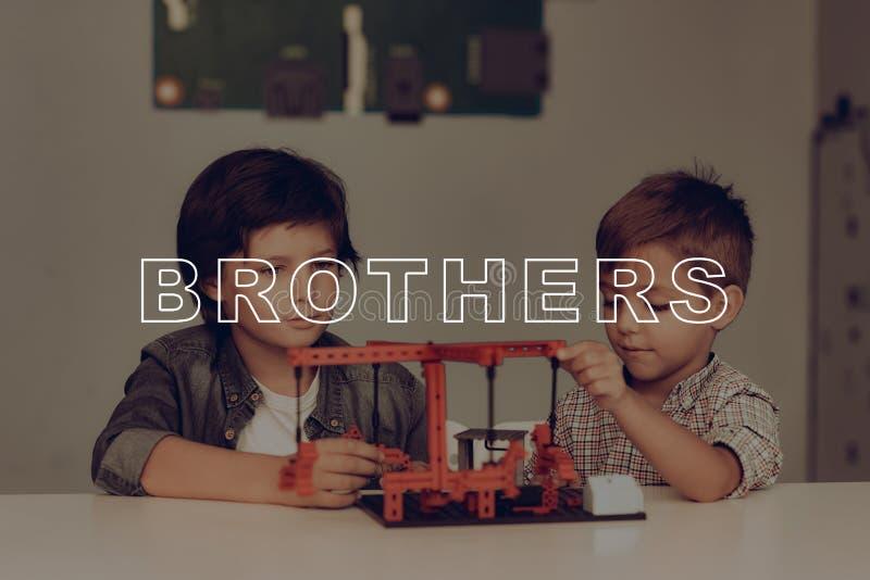 Zwei Brüder bei Grey Table Karussell-Konstruieren stockfoto