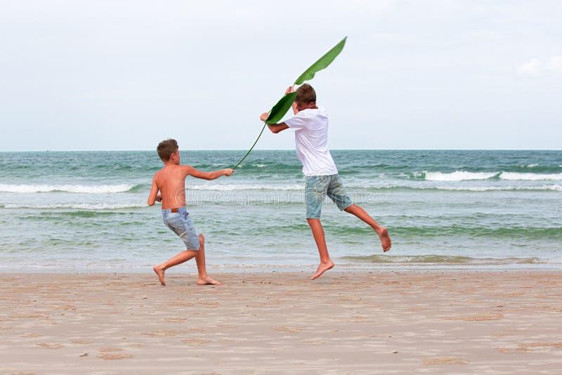 Zwei Brüder eines Jugendlichen, der auf dem Ozean, die Freundschaft O spielt stockbild