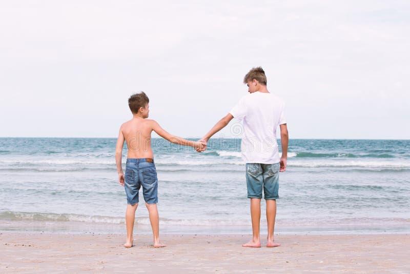 Zwei Brüder eines Jugendlichen, der auf dem Ozean, die Freundschaft O spielt lizenzfreies stockbild