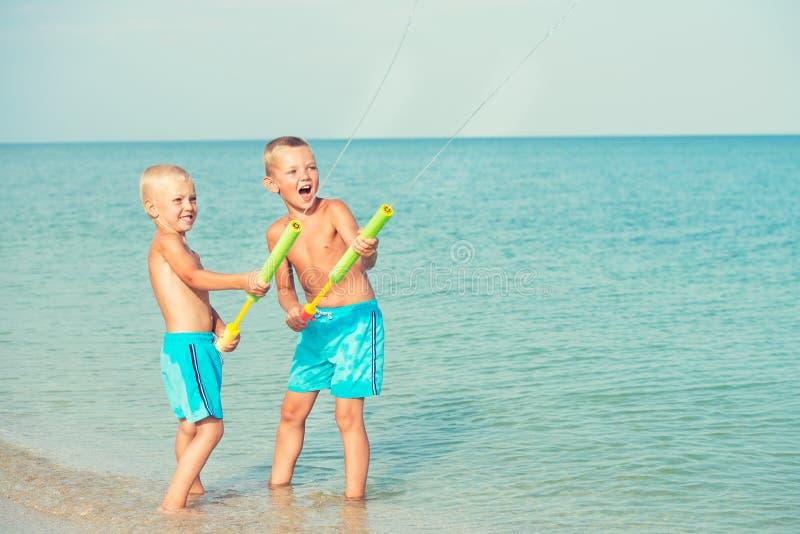 Zwei Brüder spielen auf dem Strand mit Wasserpistolen Junge Erwachsene lizenzfreie stockfotografie