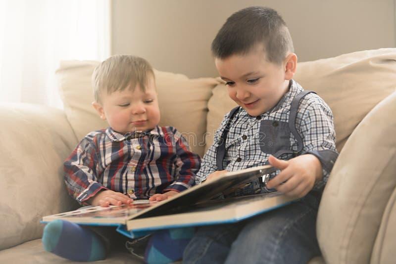 Zwei Brüder, welche die Umfassung auf der Couch sitzen, lasen ein Buch lizenzfreie stockfotos