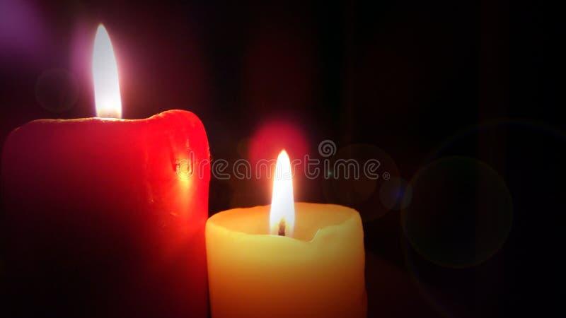 Zwei brennende Kerzen in der Dunkelheit stockbild