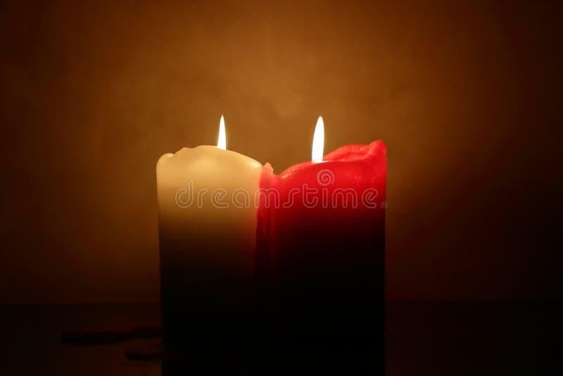 Zwei brennende Kerzen, weiß und rot lizenzfreie stockbilder