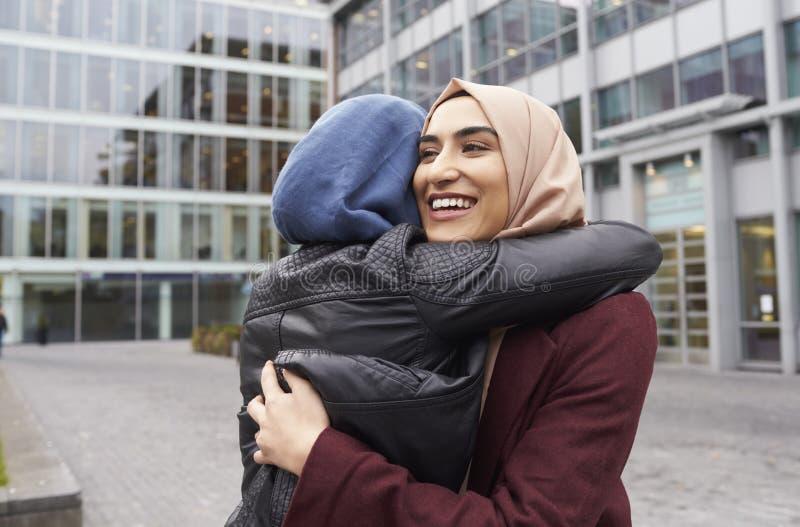 Zwei britische moslemische Freundinnen, die außerhalb des Büros sich treffen lizenzfreies stockbild