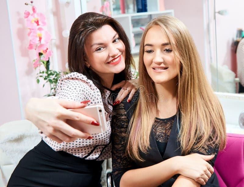Zwei brunette Mädchen und eine Blondine machen ein selfie in einem Schönheitssalon lizenzfreie stockfotografie