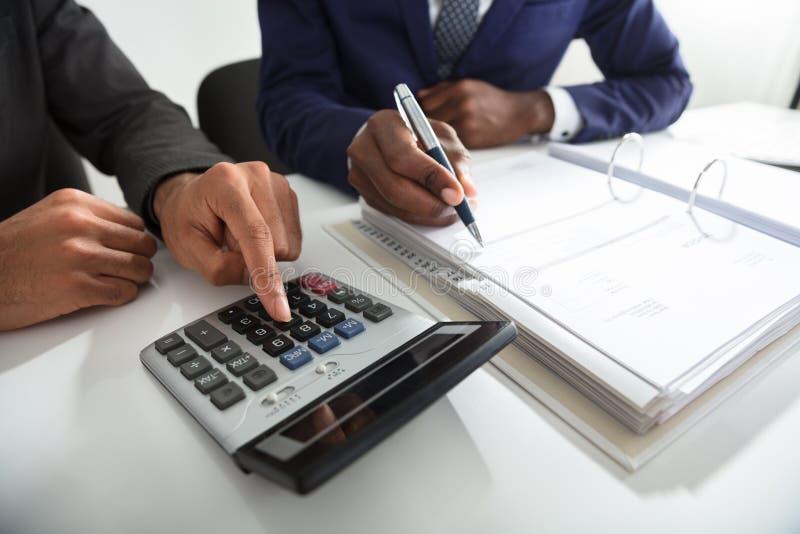 Zwei Buchhalter, die Steuer-Rechnung unter Verwendung des Taschenrechners berechnen lizenzfreie stockfotografie