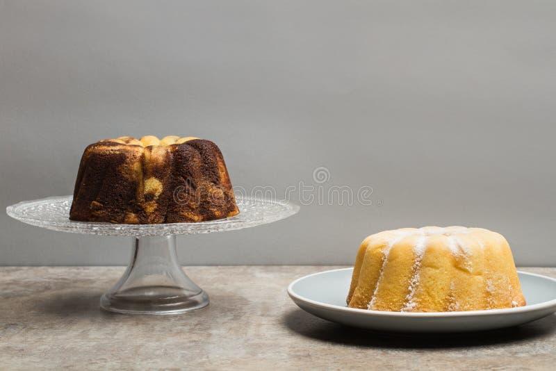 Zwei bundt Kuchen, einer von Vanille und von Schokolade und einer der Zitrone lizenzfreies stockbild